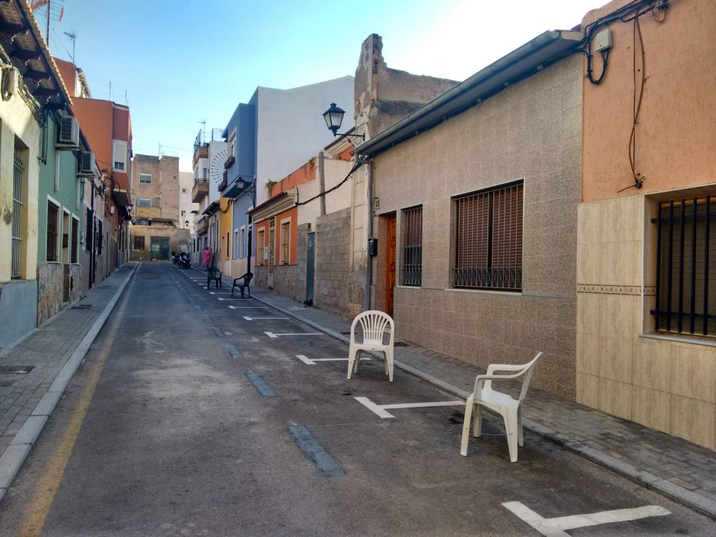 Two white plastic chairs on a street in the Latin neighbourhood of Alicante