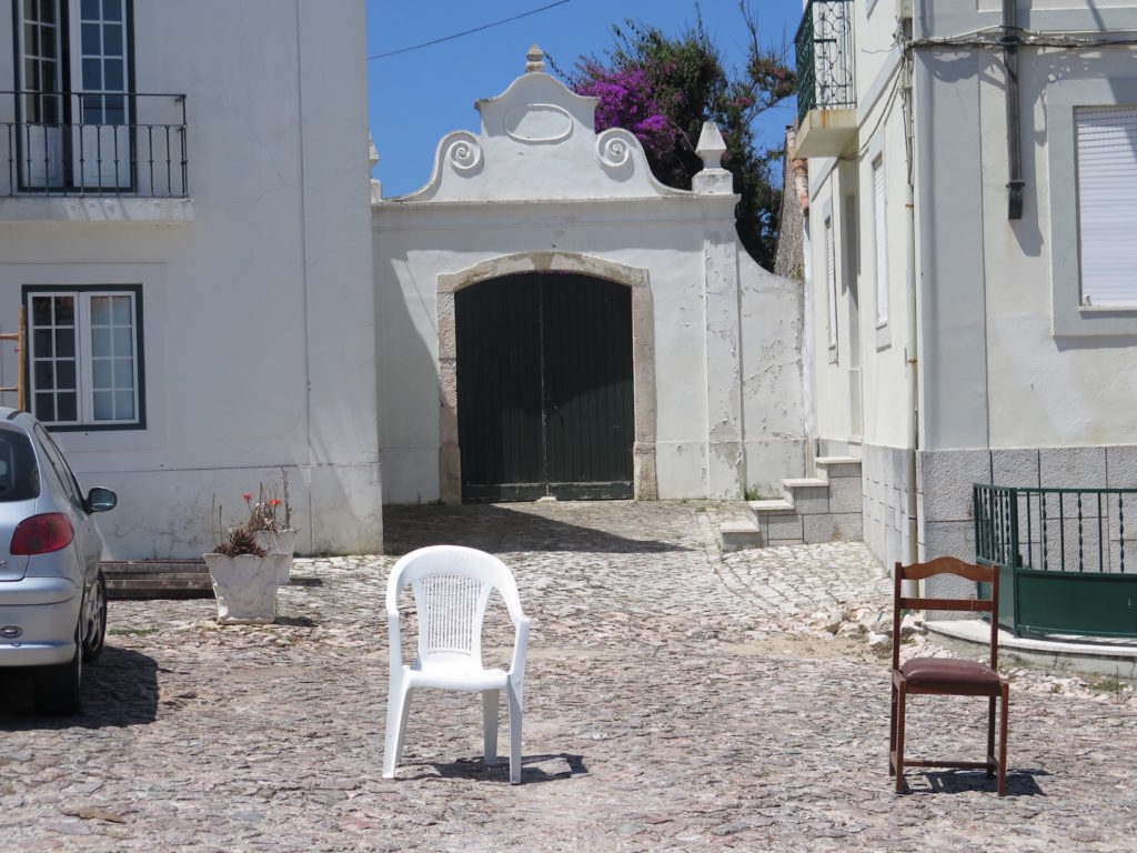 A little perspective: The white plastic chair next to it's older generation, the brown wooden chair (Nazaré)