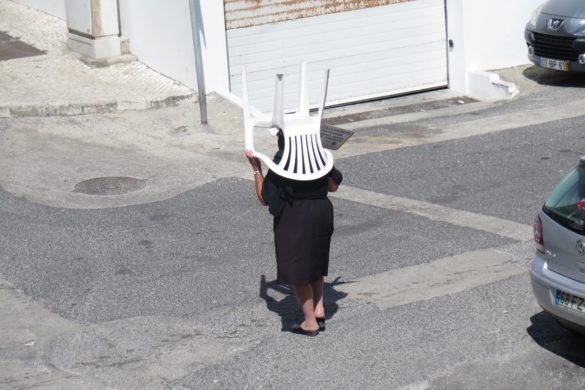 A woman carrying her white plastic chair to the beach in Nazaré