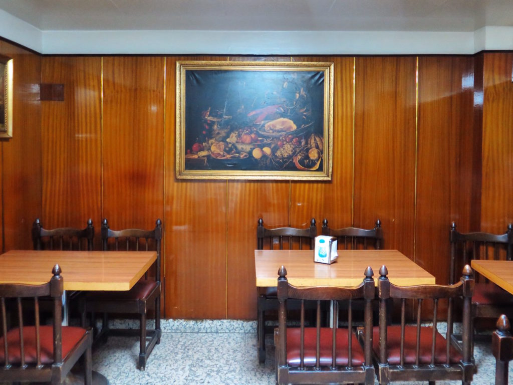 Upstairs on the mezzanine is the dining area with antique paintings