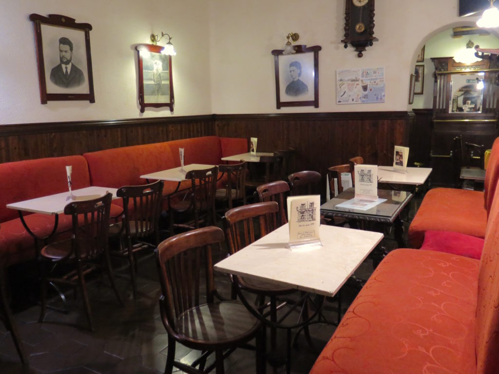 The middle room of Ajenjo Café with black and white photos of regulars and family members