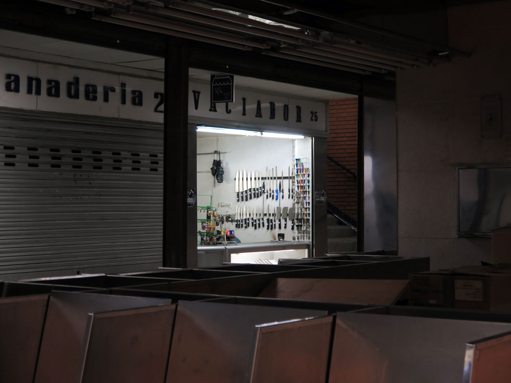A knife sharpener in an all but vacated corner of the market